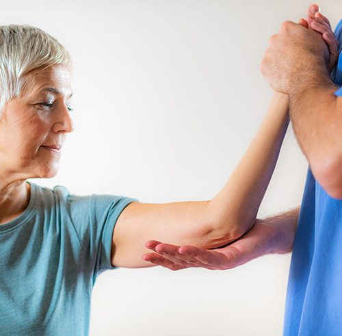 Therapieanwendung Physiotherapeut stützt Arm von Patient