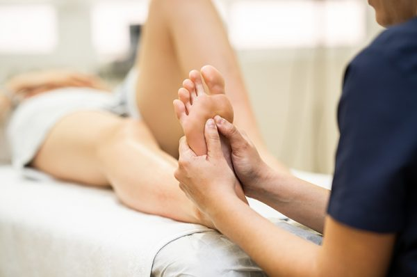 Fussreflexzonenmassage Massagen Physiotherapeut massiert Patient am Fuss
