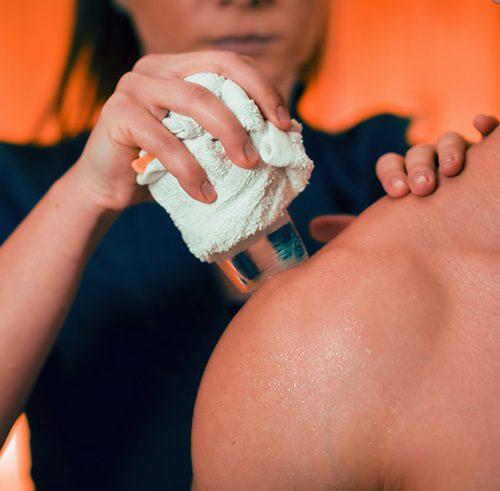 Kältetherapie Therapieanwendung Physiotherapeut legt Patient einen Kältewickel auf die Schulter
