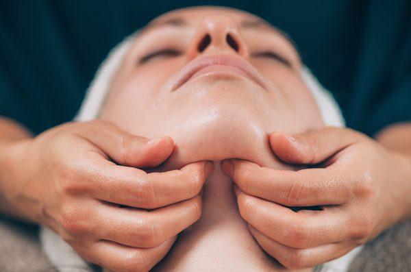 Kieferbehandlung Therapieanwendung Physiotherapeut legt Hände auf den Kiefer vom Patienten