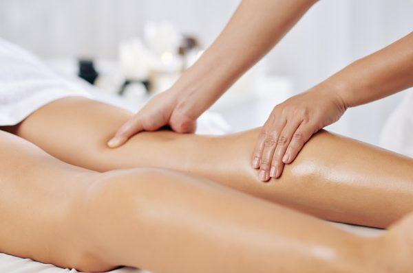 Medizinische Massage Physiotherapeut massiert Patient am Unterschenkel