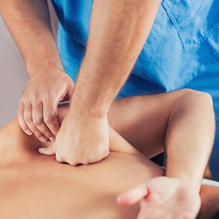 Triggerpunkttherapie Therapieanwendung Physiotherapeut massiert Schulterblatt vom Patient