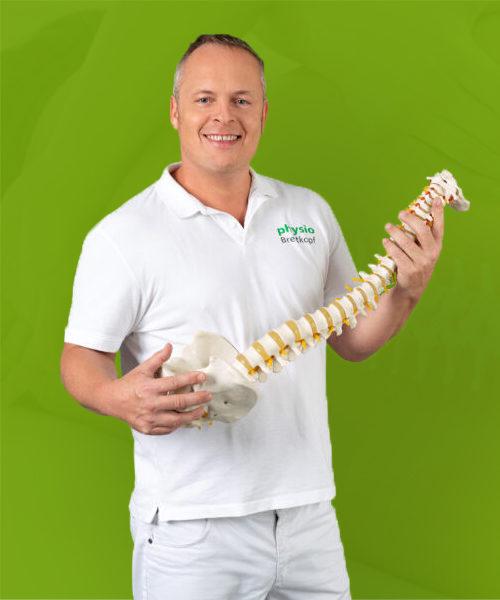 Physiotherapie Praxis Kreuzlingen Philipp Breitkopf Physiotherapeut hält Wirbelsäule in der Hand