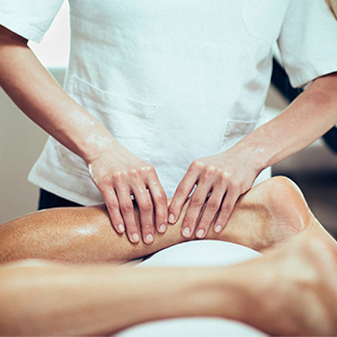Achillodynie-Therapie Therapieanwendung Patient wird vom Physiotherapeut an der Achillessehne behandelt