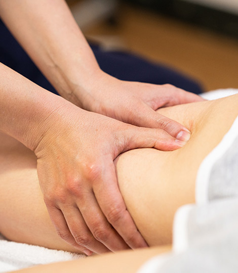 Massage Therapieanwendung Physiotherapeut massiert Patient am Oberschenkel