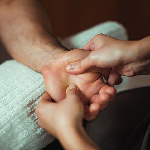 Neurologische Physiotherapie Therapieanwendung Physiotherapeut massiert Hand vom Patient