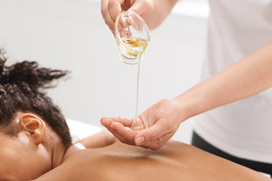 Aromaöl Massage Physiotherapeut massiert Patient am Rücken mit Aromaöl